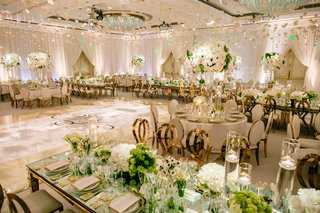 ballroom-wedding-reception-ivory-cream-mirror-table-rose-gold-chairs-green-centerpieces