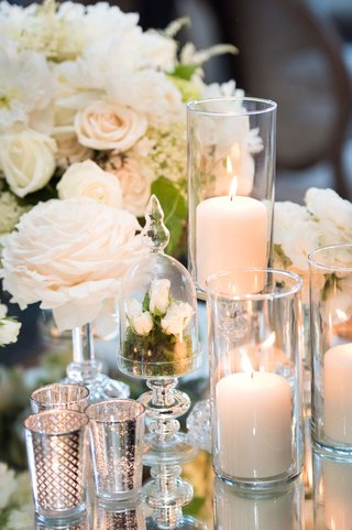 centerpieces-with-candles-in-hurricanes-mercury-votes-mirror-table-reception