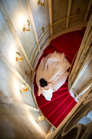 wedding-portrait-aerial-shot-of-bride-in-wedding-dress-walking-down-red-carpet-spiral-stairs