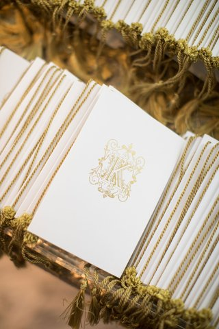 wedding-ceremony-programs-white-gold-monogram-gold-tassel-on-spine-glass-mirror-table