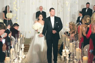 bride-in-heidi-elnora-wedding-dress-with-groom-in-tuxedo-walking-up-white-aisle-runner-candles