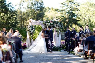 outdoor-wedding-ceremony-arch-with-drapery-and-flowers-greenery-bride-and-groom-stone-aisle-ohio