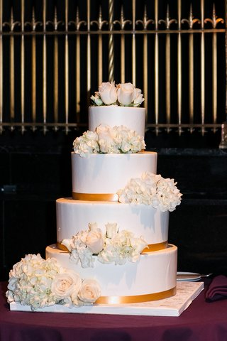 four-layer-wedding-cake-with-gold-ribbon-and-fresh-hydrangea-and-rose-flowers-on-each-layer