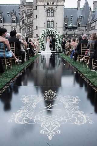 wedding-ceremony-aisle-black-runner-with-gold-monogram-crest-and-border-grass-lawn-asheville-nc