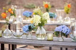 picnic-tables-topped-with-flowers-in-glass-vases-of-different-sizes