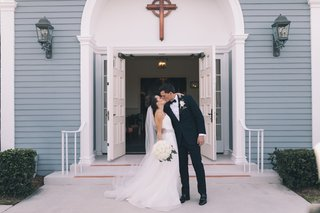 bride-in-romona-keveza-groom-in-suit-newlyweds-kiss-in-front-of-church