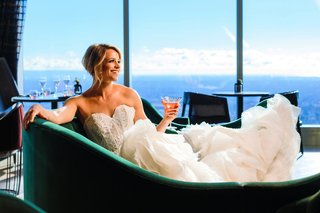 bride-in-strapless-lazaro-corset-dress-with-ruffled-train-holding-cocktail-in-emerald-green-chaise