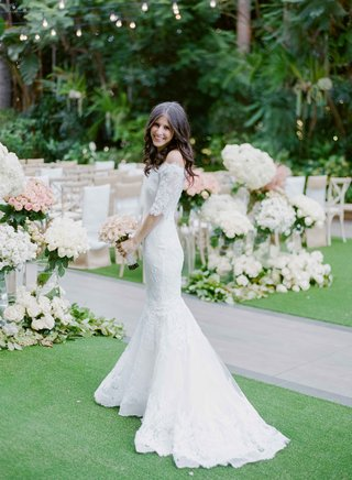 bride-in-marchesa-lace-wedding-dress-in-front-of-ceremony-decor-white-pink-flowers-garden-ceremony