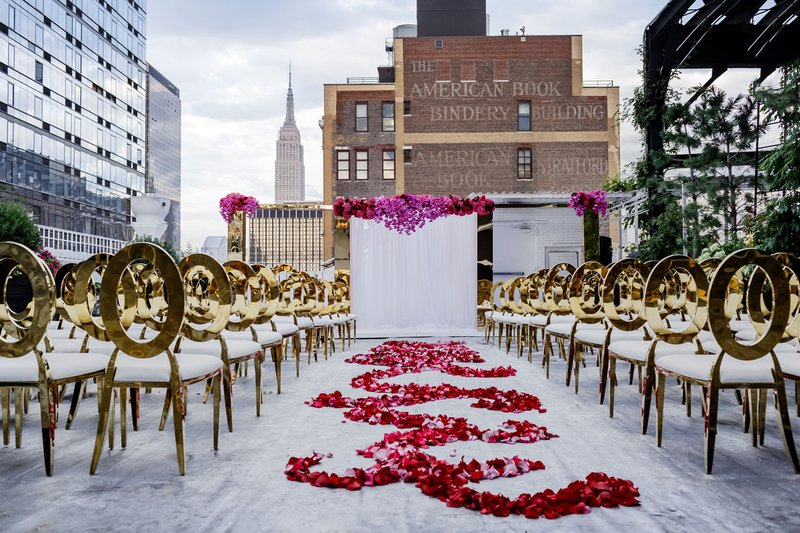 wedding ceremony rooftop new york city skyline rose petals in pattern along aisle