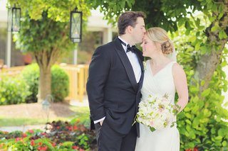 man-in-tuxedo-kisses-woman-in-wedding-dress