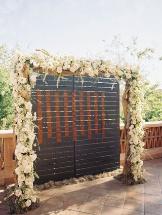 wedding-reception-wood-and-white-flowers-greenery-arch-over-dark-wood-and-leather-escort-cards