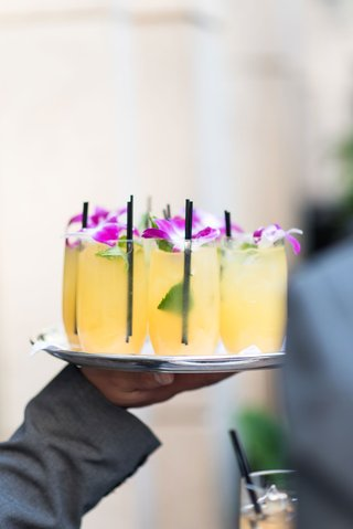 wedding-cocktail-hour-yellow-cocktail-drink-in-glass-with-black-straw-leaves-purple-flower