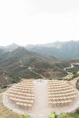wedding-ceremony-on-helipad-at-vineyard-estate-in-malibu-wood-white-chairs-flowers-at-altar-mountain