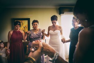 a-bride-and-her-female-family-members-hold-hands-and-pray-before-the-traditional-wedding-ceremony