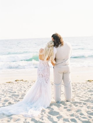 lana-and-rusev-wedding-day-looking-out-to-ocean-from-beach-wedding-lace-dress-tan-suit-vest