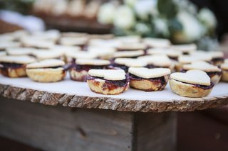 ranch-wedding-dessert-table-with-berry-tarts-topped-with-hearts-on-tree-trunk-slab
