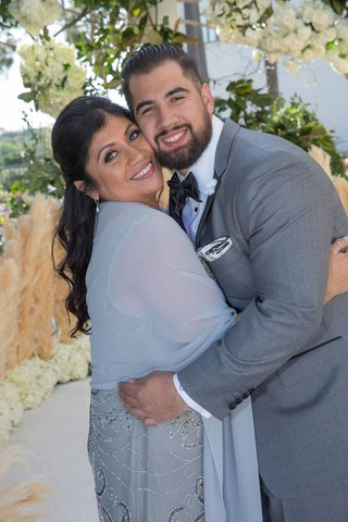 groom-in-grey-suit-and-black-bow-tie-with-mother-of-groom-in-beaded-dress-with-shawl-wrap