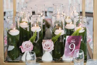 base-of-centerpiece-collection-of-floating-candles-with-leaves-wrapping-hurricanes