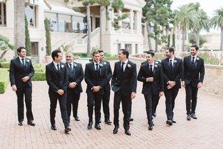groom-groomsmen-walking-black-suits-pelican-hill-resort-wedding-newport-california-sleek-mens-attire