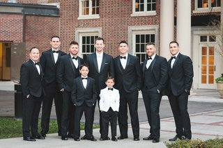 groomsmen-in-black-tuxes-with-bow-ties-ring-bearer-in-white-tuxedo-jacket-with-black-bow-tie