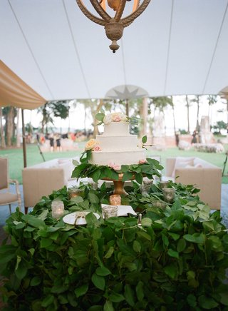 wedding-reception-tent-chandelier-over-cake-three-layer-fresh-flowers-green-leaves-covering-table