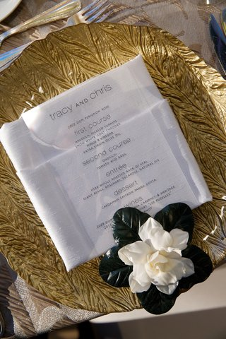 wedding-reception-place-setting-with-a-gold-textured-charger-and-white-gardenia