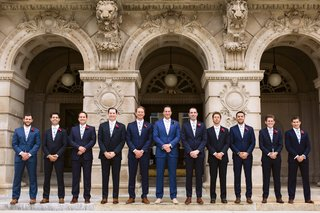 groom-and-groomsmen-in-suits-in-varying-shades-of-dark-blue