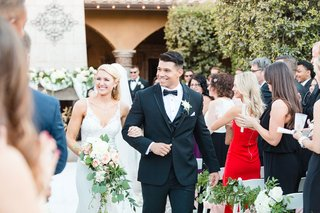 bride-in-v-neck-wedding-dress-groom-in-tuxedo-bow-tie-holding-bouquet-courtyard-outdoor-ceremony