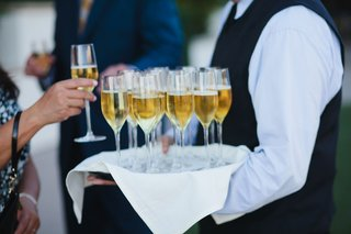 guest-grabbing-glass-champagne-flute-of-champagne-at-outdoor-cocktail-hour
