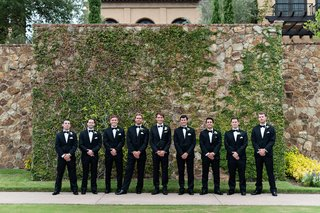 groom-and-groomsmen-in-front-of-ivy-wall