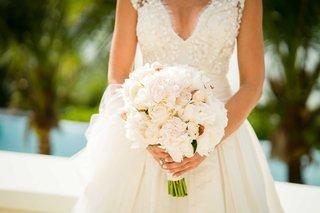 bride-in-carolina-herrera-v-neck-wedding-dress-holding-bouquet-light-flowers-white-pink-rose-peony