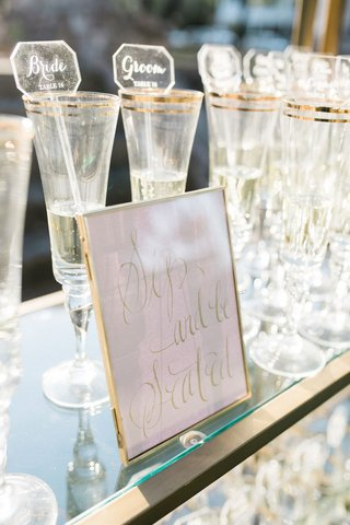 wedding-escort-cards-on-acrylic-drink-stirrers-champagne-glasses-on-gold-glass-bookcase-bookshelf