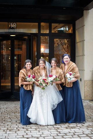 bride-in-wedding-dress-bridesmaids-in-blue-bridesmaid-dresses-brown-fur-stoles-grandmother-bouquets