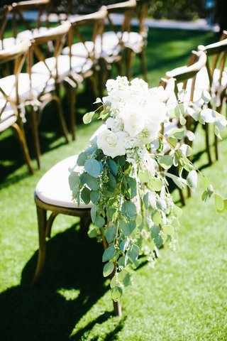 wedding-ceremony-grass-lawn-wood-chair-with-greenery-and-white-rose-flowers-on-aisle-decoration
