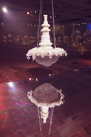 seven-tiered-wedding-cake-with-white-flowers-suspended-on-a-crystal-chandelier