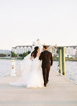 bride-and-groom-walking-on-plank-in-wedding-attire