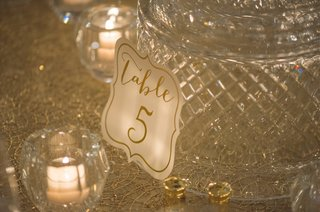 white-reception-table-card-with-gold-lettering-against-cut-crystal-by-votive-candle