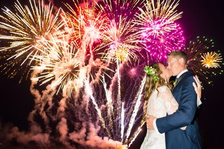 couple-kissing-underneath-fireworks-nighttime-wedding-hotel-del-coronado-reception-entertainment-sky
