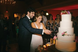 bride-and-groom-cutting-into-five-layer-wedding-cake-fresh-flowers