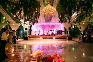 wedding-reception-watercolor-dance-floor-pink-lighting-chandelier-live-band-stage-greenery-ceiling