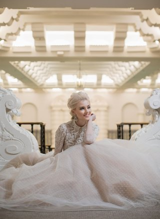 bride-sitting-down-in-long-sleeve-ball-gown-point-desprit-skirt-embellished-bodice-long-sleeves