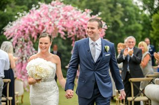 bride-in-strapless-wedding-dress-holding-groom-in-blue-suit-hand-white-peony-bouquet-pink-chuppah