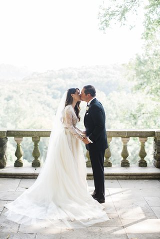 bride-in-monique-lhuillier-lace-long-sleeve-a-line-gown-cathedral-veil-kisses-groom-on-balcony