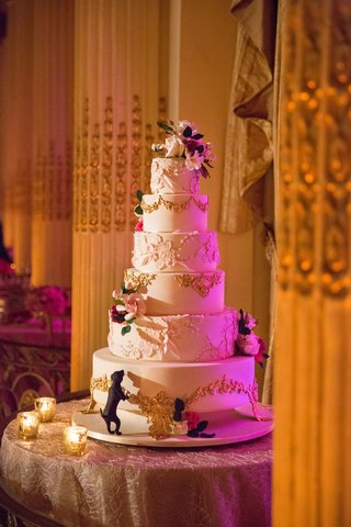 wedding-cake-with-gold-filigree-details-sugar-flowers-and-dog-puppy-biting-bottom-layer-of-cake
