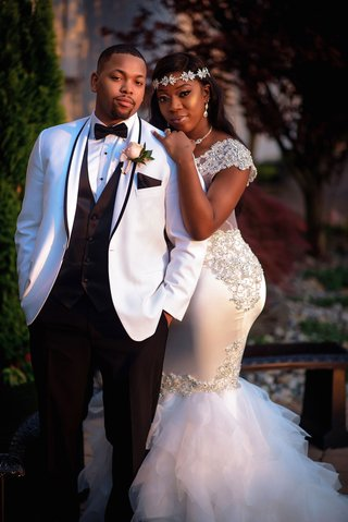 bride-in-form-fitting-mermaid-wedding-dress-with-sheer-details-headband-groom-in-white-tuxedo-jacket