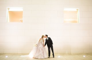 bride-in-blush-dress-kisses-groom-in-tuxedo