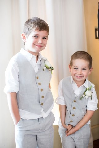 two-ring-bearers-smiling-in-white-rolled-up-sleeves-and-grey-vests-and-pants