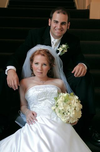 bride-leans-against-groom-on-flight-of-stairs