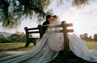 bride-and-groom-kiss-seated-on-park-bench