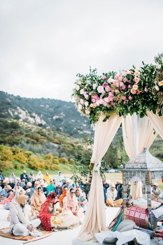 wedding ceremony arbor pink flowers greenery guests on floor for traditional ceremony view of ranch